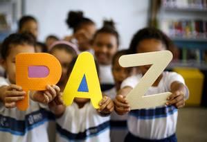 Crianças de uma turma do Colégio Municipal Walt Disney, em Ramos, que atende estudandos do Complexo do Alemão, fazem trabalhos escolares sobre a visão delas de PAZ. Foto: Fábio Rossi / Agência O Globo