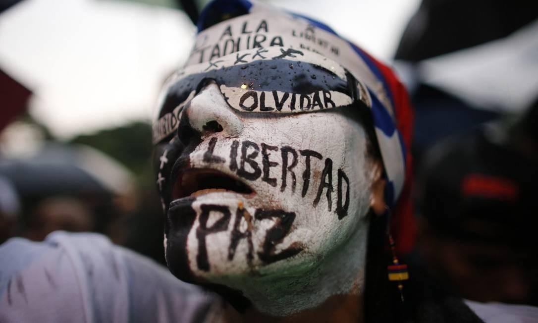 """Em vigília para homenagear mortos em protestos na Venezuela, mulher pinta o rosto com as palavras """"liberdade, paz, não esquecer"""" Foto: Ariana Cubillos / AP"""