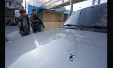 A marca do disparo no capô do carro do comerciante Foto: Marcvio Alves / Agência O Globo