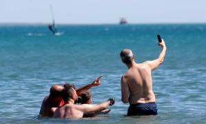 Turistas tiram uma selfie numa praia em Fos-sur-Mer, no sul da França Foto: Jean-Paul Pelissier / Reuters