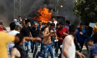 Palestinos correm após jogarem pedras contra veículos israelenses em Kubar, a oeste de Ramallah Foto: ABBAS MOMANI / AFP