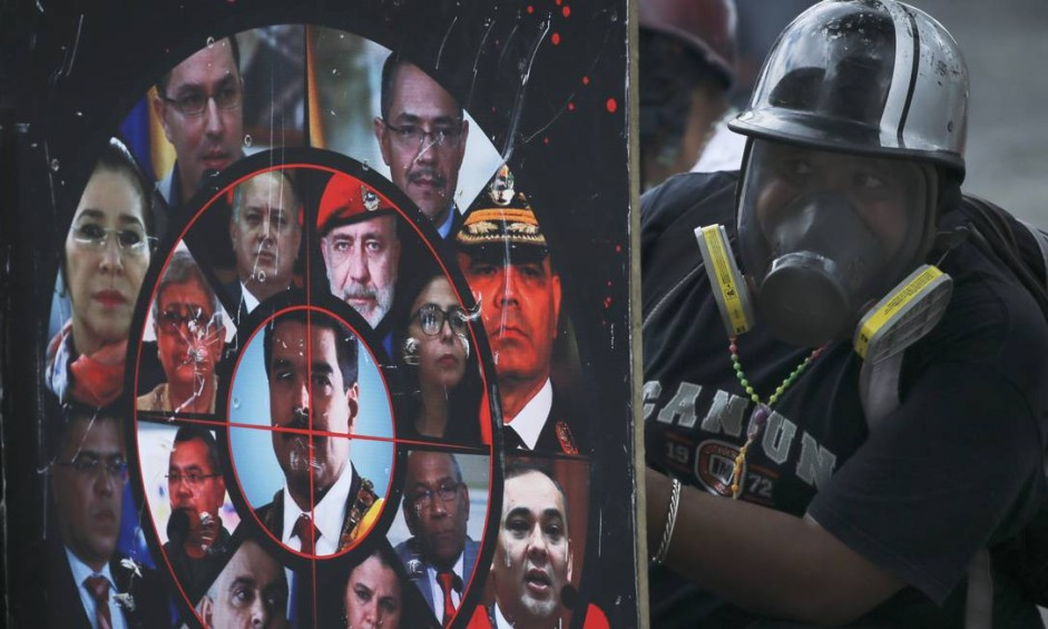 Manifestante se protege com escudo caseiro decorado com fotos do presidente Nicolás Maduro e funcionários do governo, durante protesto contra o presidente em Caracas, Venezuela Foto: Fernando Llano / AP