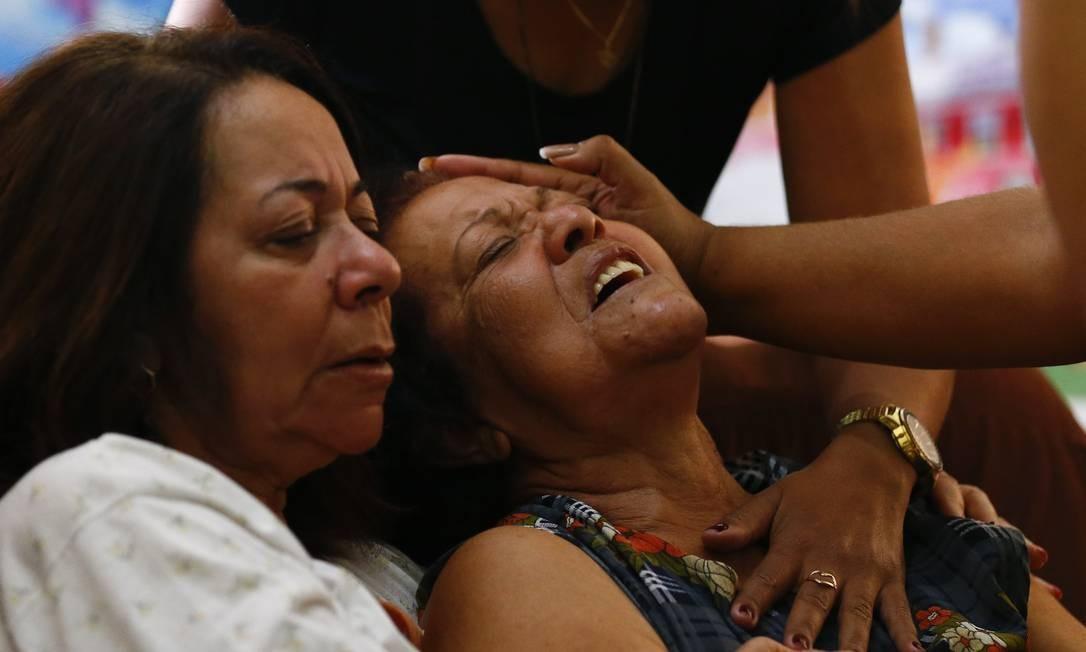 Mãe do PM é amparada na porta de casa por parentes, pouco depois de receber a notícia de que perdera o filho. 'Os policiais estão morrendo e ninguém faz nada', disse Foto: Pablo Jacob / Agência O Globo