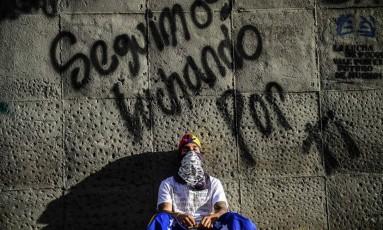 Manifestante da oposição se senta no lugar onde o jovem ativista Neomar Lander foi morto durante protestos em Caracas Foto: RONALDO SCHEMIDT / AFP