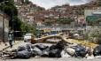 Pedestre caminha ao lado de barricada deixada por manifestantes durante greve de 48 horas na Venezuela