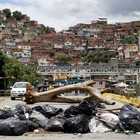 Pedestre caminha ao lado de barricada deixada por manifestantes durante greve de 48 horas na Venezuela Foto: Ariana Cubillos / AP