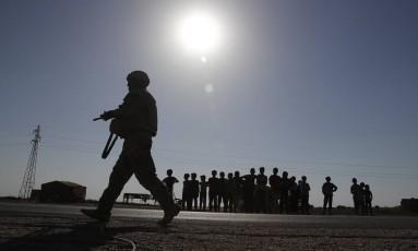 Soldado americano caminha em frente a um grupo de crianças sírias, em Raqqa Foto: Hussein Malla / AP