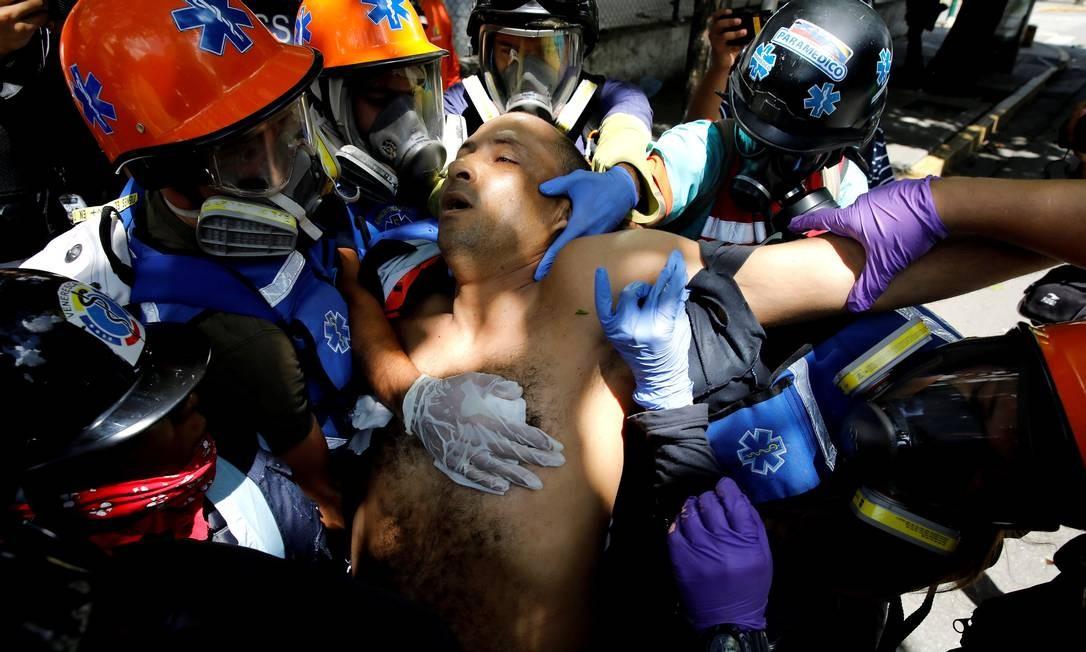 Um homem ferido durante confrontos entre manifestantes e as forças de segurança recebe atendimento médico, em Caracas Foto: CARLOS GARCIA RAWLINS / REUTERS