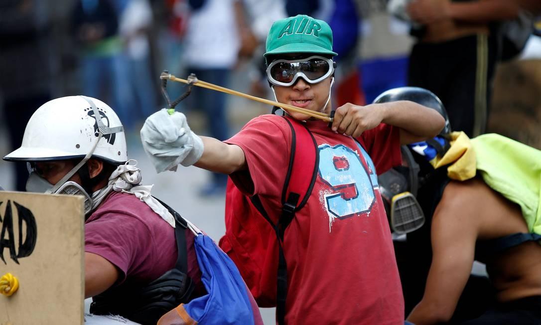 Jovem usa um estilingue durante um protesto contra o presidente venezuelano, Nicolás Maduro, em Caracas Foto: ANDRES MARTINEZ CASARES / REUTERS