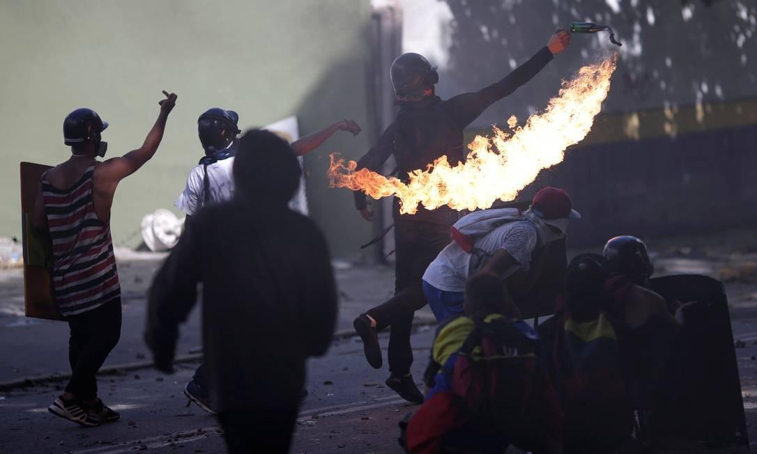 Manifestante joga bomba em um protesto durante a greve convocada pela oposição venezuelana contra o governo do presidente Nicolás Maduro Foto: UESLEI MARCELINO / REUTERS