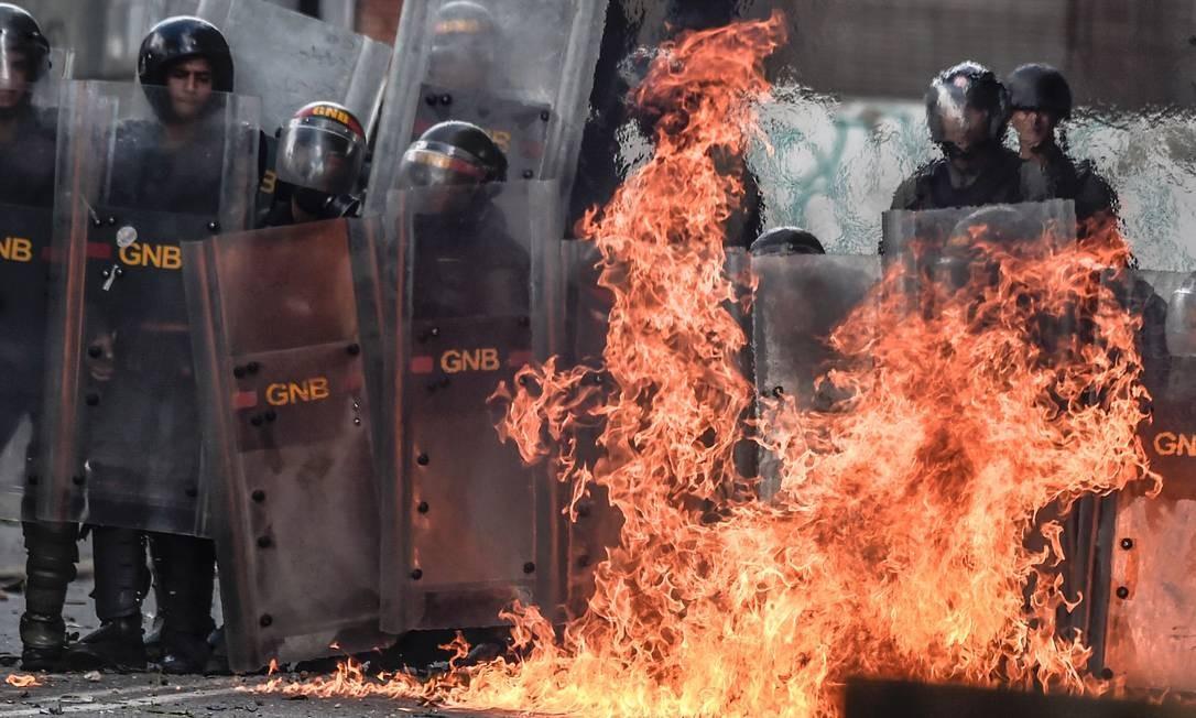 Um coquetel molotov é jogado por ativistas contra o governo e explode próximo a membros da Guarda Nacional Bolivariana (GNB) em Caracas Foto: JUAN BARRETO / AFP