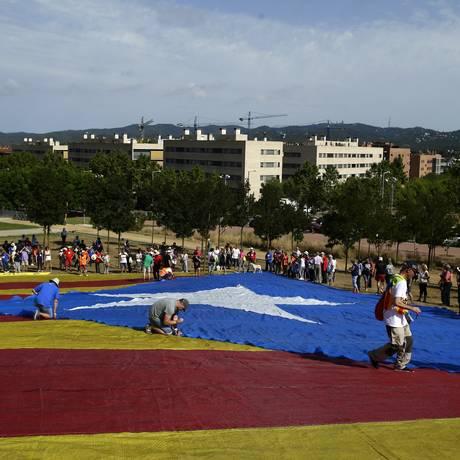 Manifestantes expõem enorme bandeira catalã em Sant Cugat del Valles, em apoio ao referendo proposto pelo Parlamento local Foto: Manu Fernandez / AP