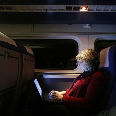 Passageira usa o computador em um trem da Amtrack, nos Estados Unidos Foto: Darron Cummings / AP/16.12.2014
