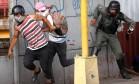 Pressão popular. Jovens encapuzados fogem de agentes de segurança enquanto um deles é preso em mais um dia de violência durante um protesto em Caracas: cinco pessoas foram mortas em dois dias de manifestações Foto: ANDRES MARTINEZ CASARES/REUTERS