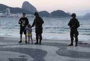 """Paisagem diferente. Na Praia de Copacabana, onde se concentram turistas, militares que patrulham a orla posam para fotos a pedidos: população não resistiu a """"selfies"""" Foto: Pablo Jacob / Agência O Globo"""