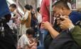 Passageiros consultam seus celulares no metrô em Wuhan, na região central da China: governo endurece ações para restringir a internet