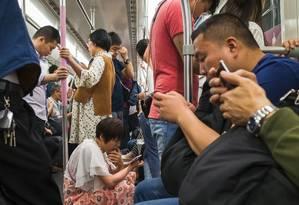 Passageiros consultam seus celulares no metrô em Wuhan, na região central da China: governo endurece ações para restringir a internet Foto: AFP/Pan Weijun