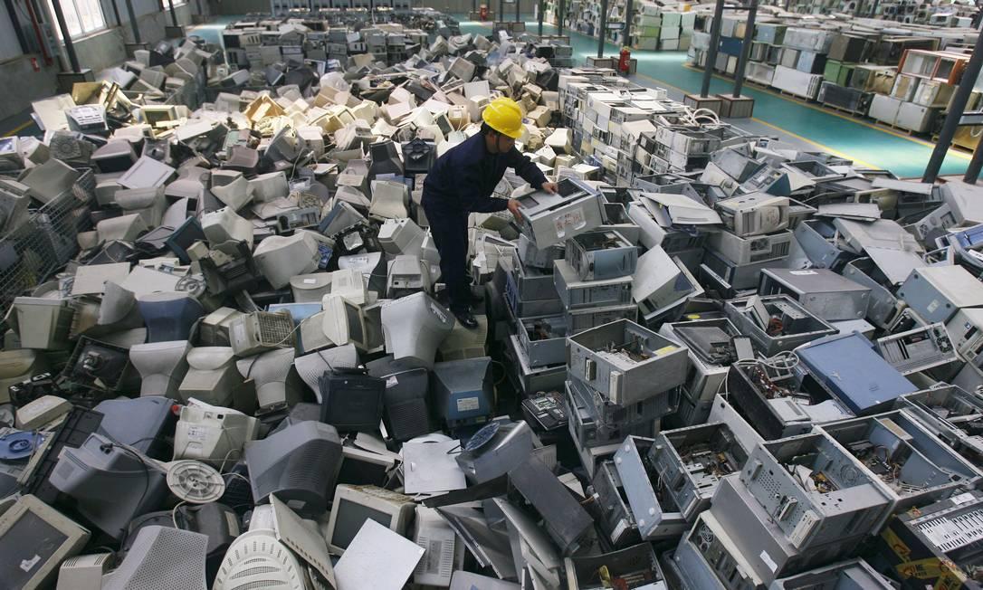 Funcionário arruma computadores descartados em depósito de lixo eletrônico na China: desperdício ajuda a adiantar data Foto: Reuters