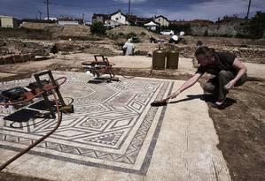 Um arqueólogo trabalha em um mosaico no local da antiguidade arqueológica de Sainte-Colombe, perto de Vienne, na França Foto: JEAN-PHILIPPE KSIAZEK / AFP/Getty Images