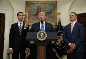 O presidente americano Donald Trump, fala ao lado dos senadores republicanos Tom Cotton (à esq.) e David Perdue (à dir.), no Salão Roosevelt na Casa Branca Foto: Evan Vucci / AP