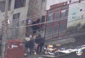 Homem com um fuzil dá cobertura a outros que carregam mercadoria roubada Foto: Reprodução / TV