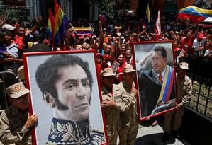 Mudança de cenário. Membros da Milícia Bolivariana carregam retratos de Simón Bolívar e Hugo Chávez para realocá-los no Palácio Legislativo, onde novo superpoder funcionará Foto: CARLOS GARCIA RAWLINS / Carlos Garcia Rawlins/REUTERS