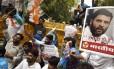 Apoiadores do Partido do Congresso seguram cartazes com fotos de Rahul Gandhi, um dos lideres da agremiação, que teve seu carro atacado por multidão enfurecida
