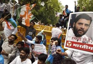 Apoiadores do Partido do Congresso seguram cartazes com fotos de Rahul Gandhi, um dos lideres da agremiação, que teve seu carro atacado por multidão enfurecida Foto: AFP/DOMINIQUE FAGET