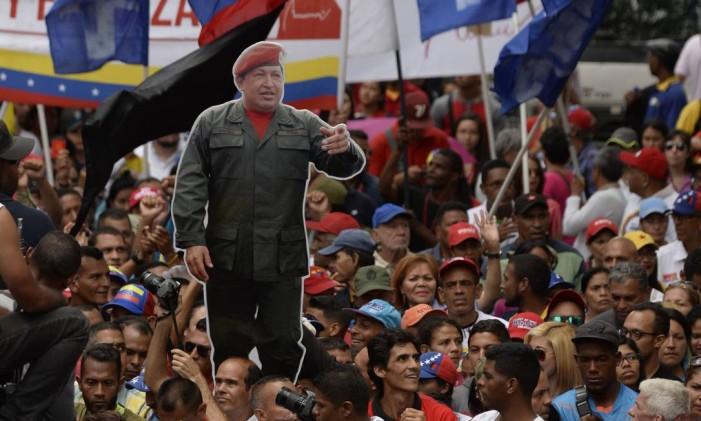 Onipresente. Simpatizantes do chavismo se manifestam carregando bandeiras e imagens do falecido presidente Foto: FEDERICO PARRA / Federico Parra/AFP