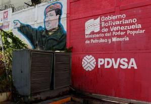Logo da companhia estatal de petróleo venezuelana PDVSA é visto próximo a um mural com um grafite do presidente Hugo Chávez, em Caracas Foto: CARLOS GARCIA RAWLINS / REUTERS