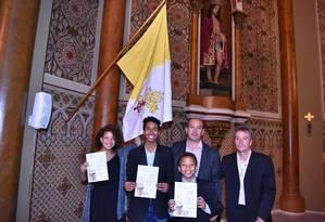Os três filhos de Toni Reis e David Harrad mostram, orgulhosos, suas certidões de batismo Foto: Arquivo pessoal
