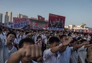 Todos pelo regime. Norte-coreanos marcham em apoio a Kim Jong-un no embate retórico contra os EUA: ditador ameaça lançar mísseis a poucos quilômetros de distância de ilha americana no Pacífico, gesto que desataria guerra Foto: KIM WON-JIN / AFP/Kim Won-jin