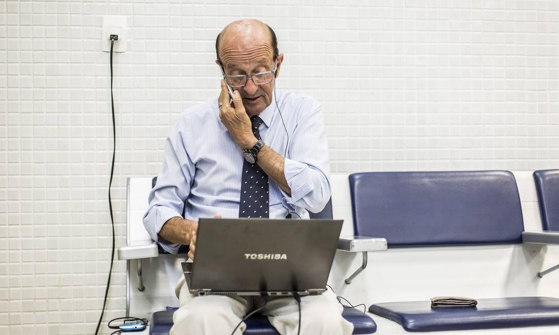 Ele carrega o laptop enquanto fala ao telefone com alguém que o fazia uma proposta de emprego Hermes de Paula / Agência O Globo