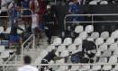 No fim do jogo, a polícia teve que conter torcedores uruguaios, que quebraram e jogaram cadeiras no campo Foto: Marcelo Theobald