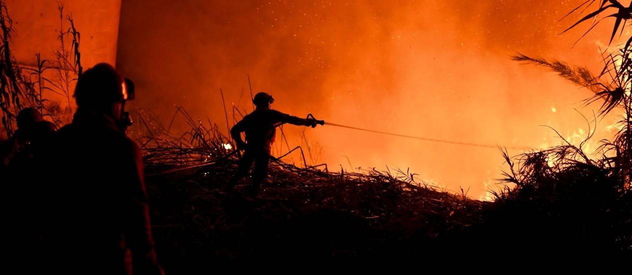 Bombeiros trabalham para combater as chamas na aldeia de Rio de Moinhos, na região de Abrantes Foto: PATRICIA DE MELO MOREIRA / AFP
