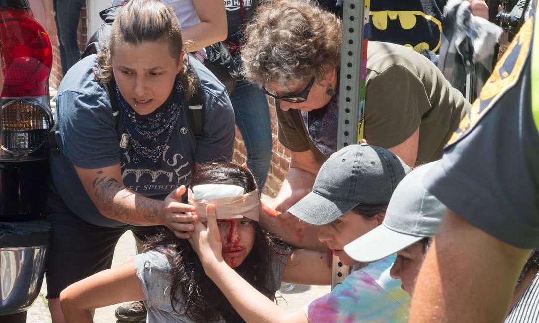Pessoas recebem primeiros socorros após um carro atropelar uma multidão de manifestantes PAUL J. RICHARDS / AFP