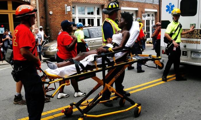Equipes de emergência transportam uma vítima que foi ferida quando um caro atropelou um grupo de manifestantes no marcha