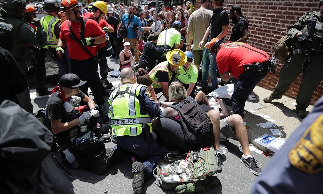 Socorristas atendem pessoas feridas após um carro atropelar uma multidão de manifestantes antifascistas que protestavam no centro da cidade CHIP SOMODEVILLA / AFP