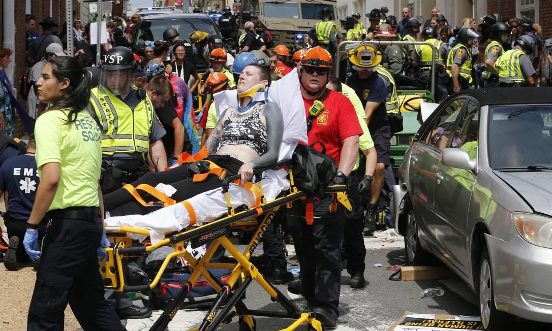 Socorristas atendem pessoas feridas após um carro atropelar um grupo de manifestantes em Charlottesville, na Virgínia Steve Helber / AP
