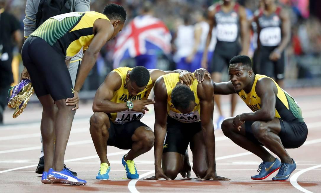 Bolt é consolado pelos companheiros de revezamento LUCY NICHOLSON / REUTERS