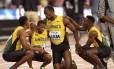 Bolt é consolado pelos companheiros ao não completar a prova no seu adeus às pistas