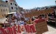 """Morador exibe cartaz que diz """"Eu não quero ir embora, vou ficar"""", em protesto em Veneza: governo ameaça restringir número de turistas na cidade"""