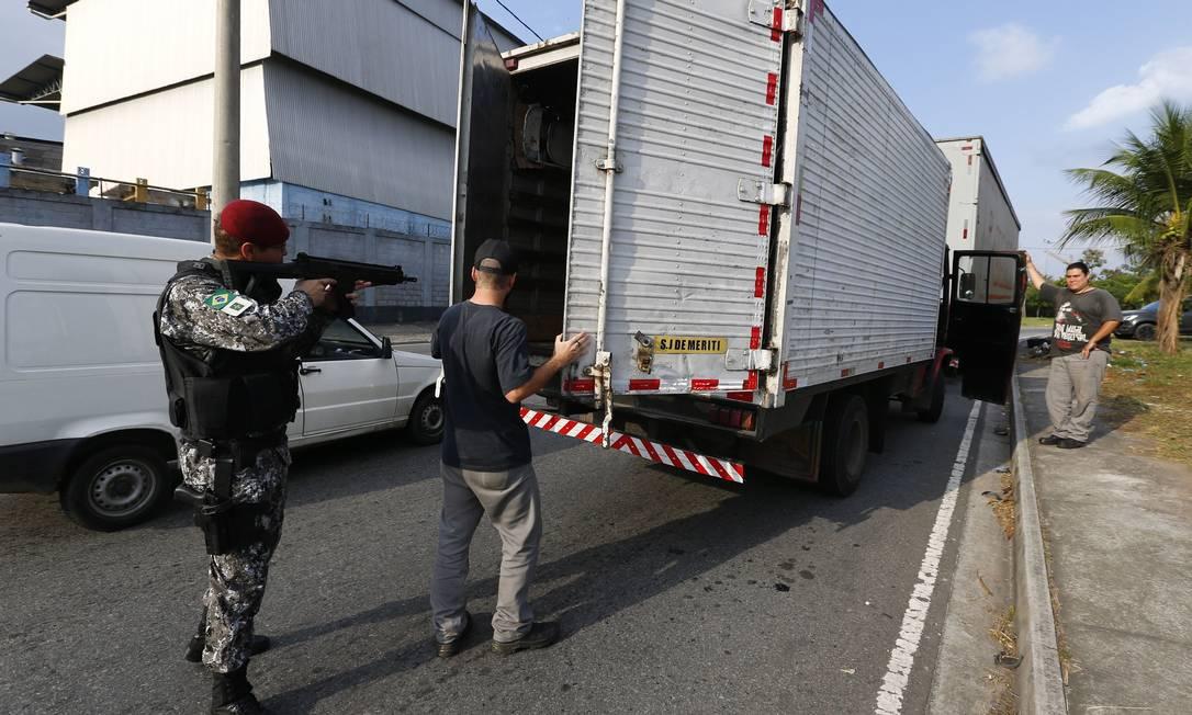 Um motorista abre o baú de seu caminhão para uma revista na saída da Via Dutra para a Pavuna: à noite, ações policiais são raras Foto: Pablo Jacob / Agência O Globo