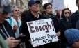 Ativista segura cartaz pedindo o impeachment de Trump por inação contra grupos neonazistas