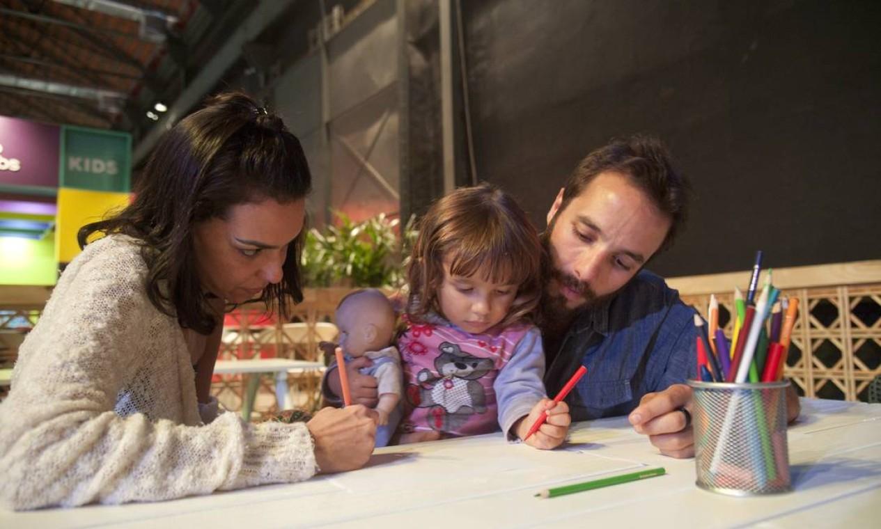 O chef Elia Schramm com a filha Olivia e a namorada, Ana Paula Auger, desenhando no Espaço Kids Foto: Adriana Lorete / Agência O Globo