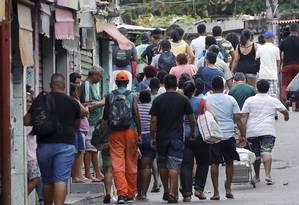 Moradores do Jacarezinho se amontoam em rua, na entrada da favela, à espera de fim de tiroteio entre traficantes e policiais. Foto: Domingos Peixoto / Agência O Globo