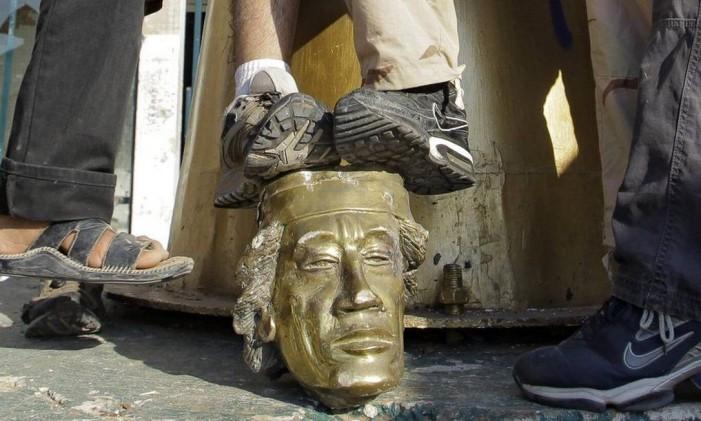 Cabeça da estátua de Kadafi é pisada após derrubada da imagem Foto: Reprodução