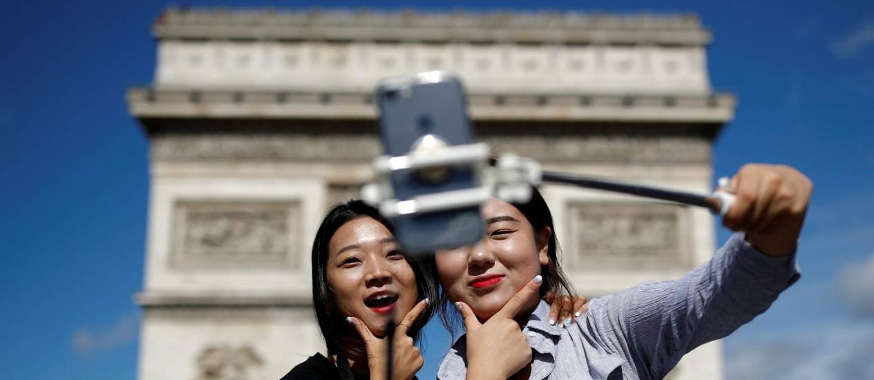 Turistas tiram selfie em frente ao Arco do Triunfo, em Paris Foto: Christian Hartmann / Reuters