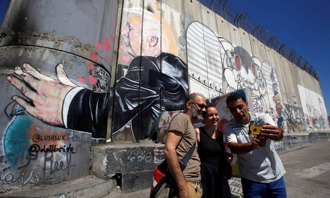 Dá para fazer selfie até mesmo em frente aos polêmicos muros da Cisjordânia, com direito à participação de Donald Trump Foto: Mussa Issa Qawasma / REUTERS