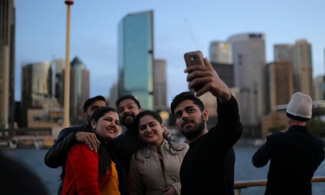 Grupo de turistas faz uma selfie a bordo da barca Manly, em frente ao Circular Quay, no porto de Sydney, na Austrália Foto: Steven Saphore / REUTERS